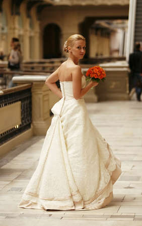 debutante: The beautiful bride with bouquet in an interior