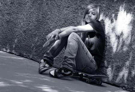 in trouble: La chica con la sesi�n de skate contra una pared. Sombra en la pared como un ala