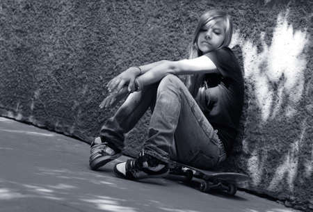 troubles: The girl with skateboard sitting against a wall. Shadow on a wall as a wing Stock Photo