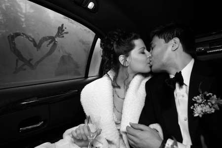 The groom and the bride kiss in the car. On glass heart is drawn. bw