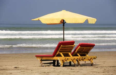 invitando: Invitar a las sillas de madera en una playa de Bali Foto de archivo