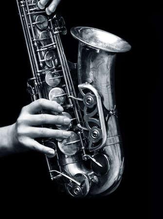 melodies: Saxophone player on black background. bw+blue tone Stock Photo