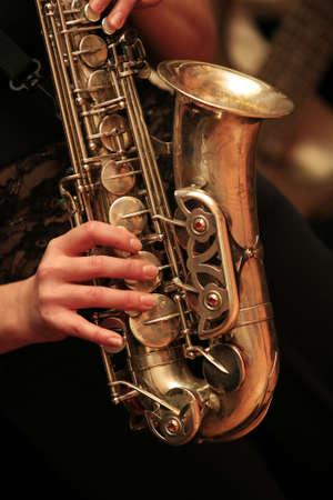 melodies: Saxophone player on dark background.