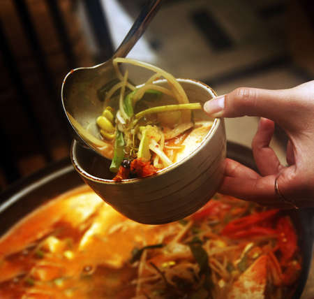 Delightful healthy Asian kitchen - magnificent and nutritious Korean soup with noodles and seafoods
