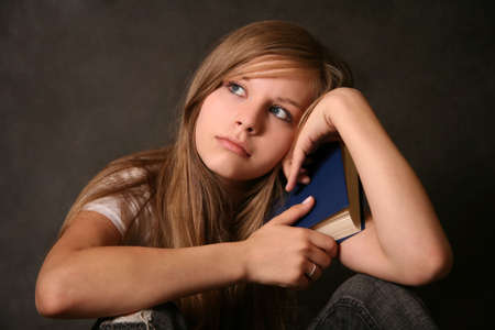 Young student girl with books on dark backgrounds photo