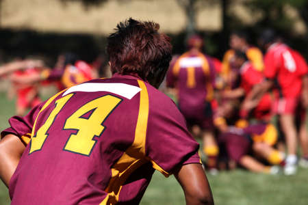 Rugby player in action on a background of players