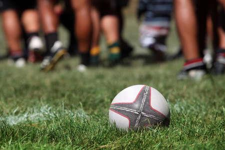 and rugby ball: Un bal�n de rugby de c�sped sobre un fondo de las piernas de los jugadores