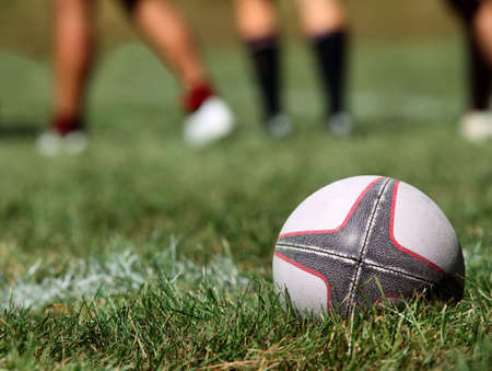 rugby ball: Rugby ball on a grass on a background of legs of players