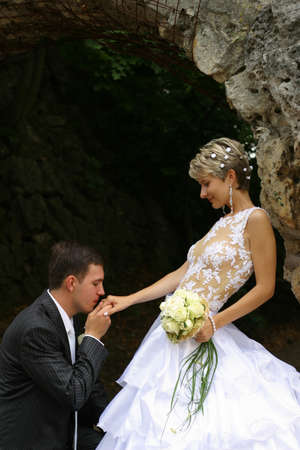 amorousness: The groom kisses a hand to the bride kneeling