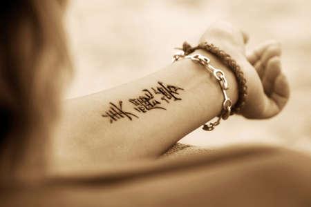 Bracelets: A womans hands with a beautiful henna tattoo. Hieroglyph  Stock Photo