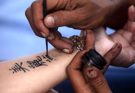 Artist draws a tattoo henna on a female hand. Hieroglyph  photo