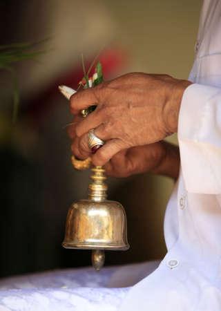 familia orando: Campana ceremonial en las manos del sacerdote