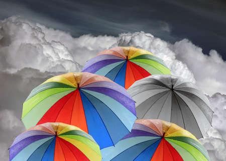 Rainbow umbrellas against blue sky