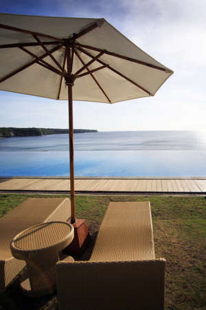 dreamland: Wicker chairs on a Dreamland beach. The edge of pool merges with ocean