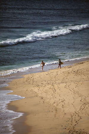 dreamland: Two girls with boards for surfing at coast of the Indian ocean. Dreamland beach - Bali