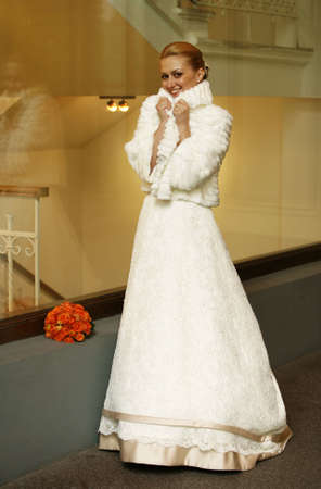 The beautiful frozen bride in a white fur coat photo
