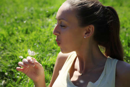 Girl enjoying summertime at a lawn of dandelions photo
