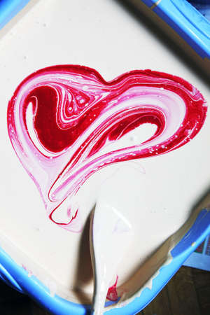 stirred: White oil paint in a blue basin with the red paint stirred as heart