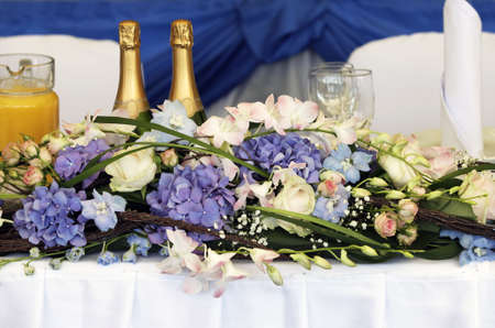 Close up of beautifully laid tables at wedding reception venue, focus on bouquet of flowers. photo