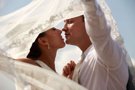 The groom and the bride kiss having closed by a veil Stock Photo - 5295591