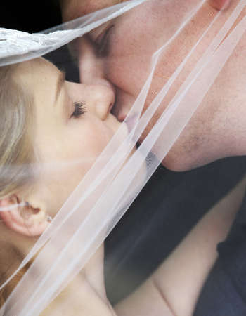 getting a bride: The groom and the bride kiss having closed by a veil