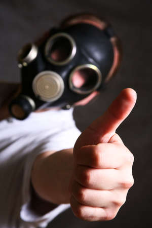 The person in a gas mask. A hand in a zone of sharpness photo