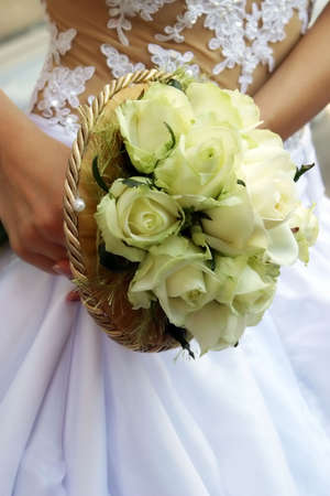 Wedding bouquet from white roses in a hand of the bride