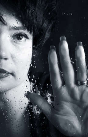 Portrait of the beautiful brunette behind wet glass photo