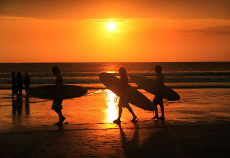 Silhouettes of three surfers at red sunset. Kuta beach, Bali, Indonesia