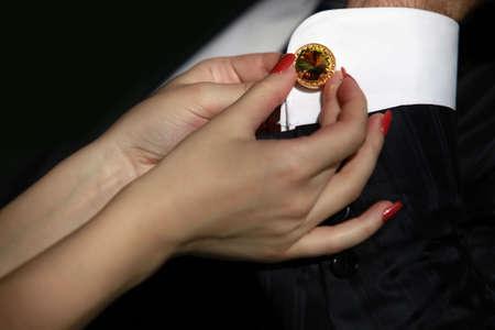 cufflink: Bride fastening a cuff-link before getting married