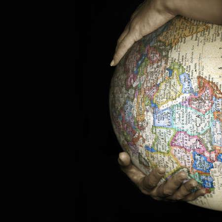 Bauch der schwangeren Frau mit einer Textur einer Karte der Welt Lizenzfreie Bilder