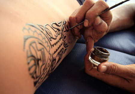 Artist draws a tattoo henna on a male body. photo