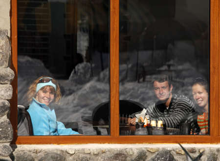 Three friends in cafe behind glass in which winter is reflected photo