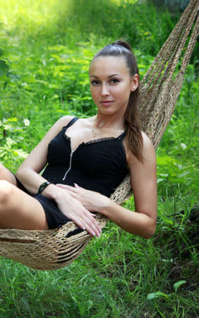 The young woman enjoys laying in a hammock photo