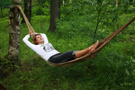rest: The woman enjoys laying in a hammock