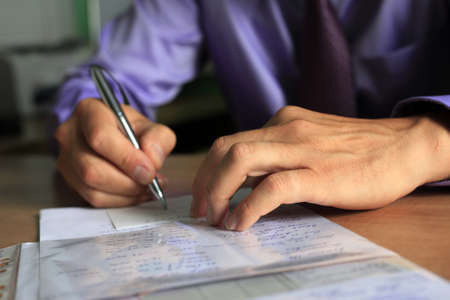 businessman signing documents: Hand of the businessman with pen