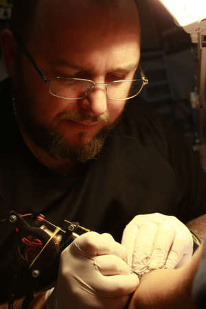 A tattoo artist applying his craft onto the hand of a female photo