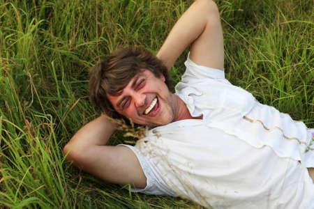 weakening: The laughing adult the man weakening in a grass
