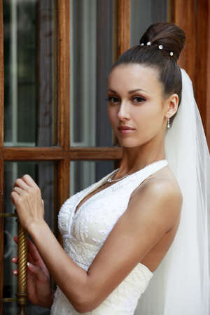 The beautiful bride about a door. Natural illumination Stock Photo - 7582362