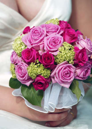 Wedding bouquet from roses on a background of a dress photo