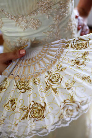Hand of the bride with an open fan with gold flowers photo