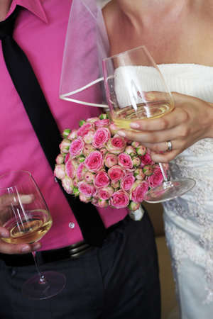 Bouquet of flowers on a background of a dress of the bride and a suit the groom.  Stock Photo - 7582612