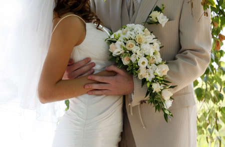 bridal bouquet: Bouquet of flowers on a background of a dress of the bride and a suit the groom.