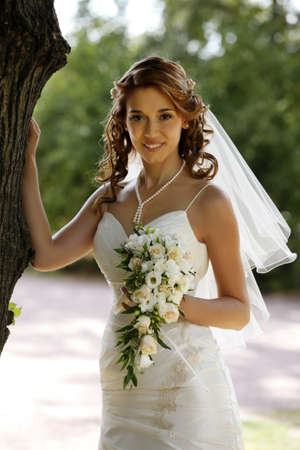 The beautiful bride with bouquet in park Stock Photo - 7696300