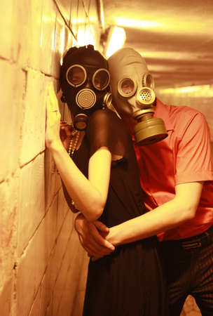 Married couple in gas masks in a tunnel photo