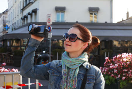 Girl using camcorder in the street Paris photo