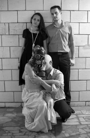 Two married couples in a tunnel, one of pairs in gas masks photo