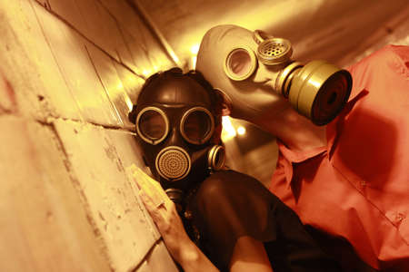 Married couple in gas masks in a tunnel Stock Photo - 7933620