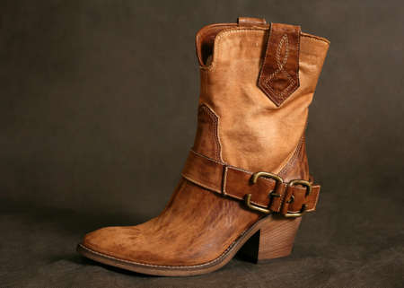 Female boots of the cowboy close-up on a dark background photo