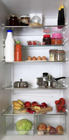 The refrigerator, filled with different food stuffs photo